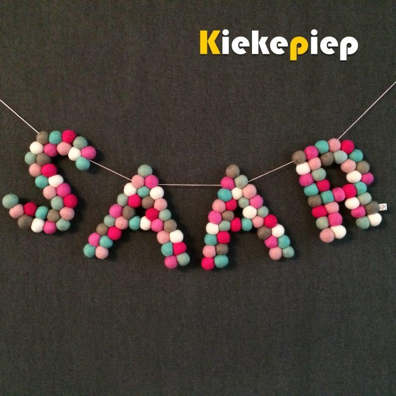 Naamletters van viltballetjes mint roze